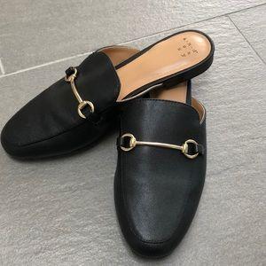 Black flat mules.